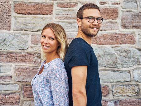 Glückliches Paar Rücken an Rücken und lächelnd in die Kamera vor Brick Wall Background