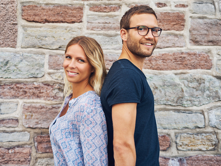 facing away: Happy Couple Standing Back to Back and Smiling at the Camera Against Brick Wall Background Stock Photo