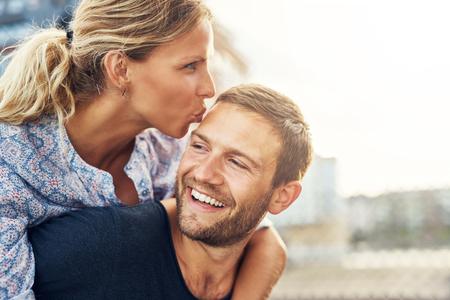 여자 키스 남자 그는 웃음 동안, 젊은 커플
