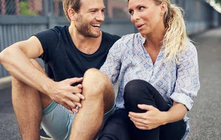 camaraderie: Couple having a good time while sitting on the ground