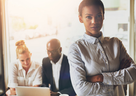 Erfolgreiche junge schwarze Business-Frau vor der multi-ethnische Gruppe von Menschen stehen