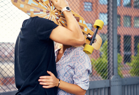 tantalizing: caressing couple hiding behind skateboard and kissing