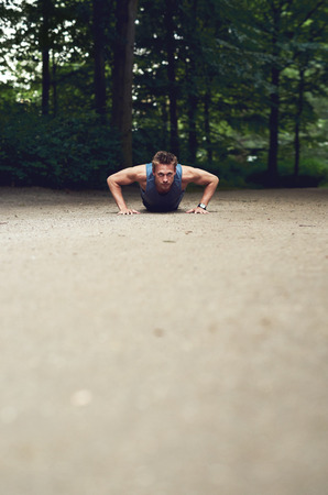 regime: Low angle view of a fit young man doing press-ups in a park as part of his daily exercise regime, with foreground copyspace