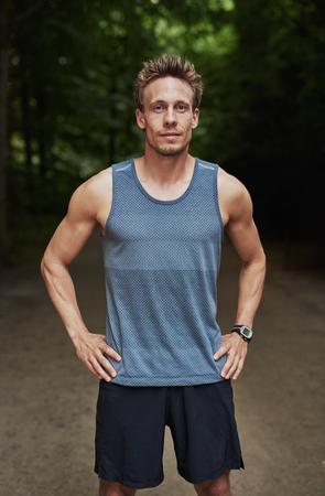 deportistas: Hombre muscular atlética en ropa deportiva de pie con las manos en las caderas al aire libre en un parque mirando a la cámara mientras se toma un descanso de su entrenamiento