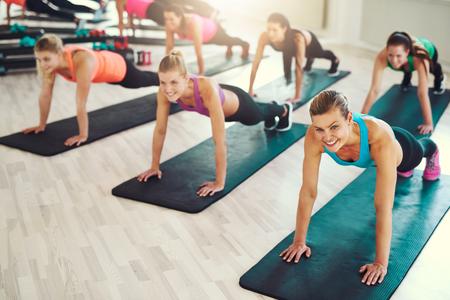 salud y deporte: Gran grupo de mujeres jóvenes que se resuelve en un gimnasio haciendo flexiones en una clase de aeróbic en un concepto de salud y estado físico