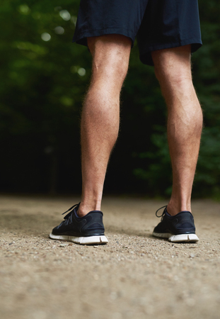 back exercise: Rear view of the legs of a fit muscular athletic man with toned calves standing outdoors in his sportswear