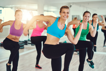 fitness, sport, training, aerobics and people concept - group of people working out in gym