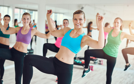 people exercising: Group of enthusiastic young women in bright colored clothes practicing aerobics in a gym in a health and fitness concept Stock Photo