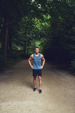 high angle: Athletic young man in sportswear standing waiting in a park with his hands on his hips looking up at the camera, high angle full length view
