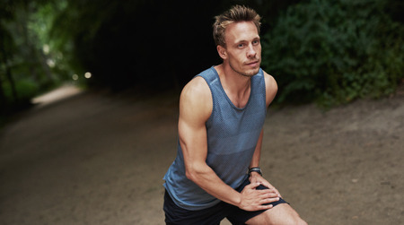wooded: Athletic handsome man warming up before his workout or jog doing stretching exercises outdoors on a track in a wooded park Stock Photo