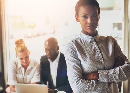 Succesvolle jonge zwarte zakenvrouw staande voor multi-etnische groep mensen
