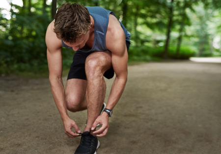 bending down: Fit muscular male jogger bending down tying his shoe laces in a track through a lush wooded park in a healthy lifestyle concept