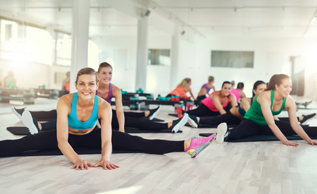 and activities: Group of fit women stretching and exercising in a fitness class, aerobics and fitness concept