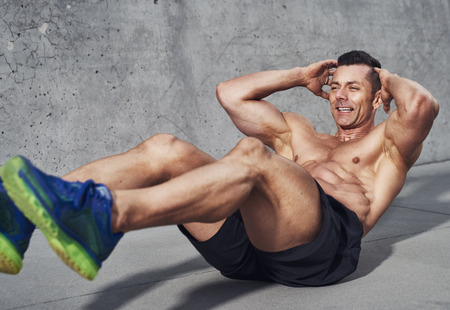 fit: Muscular male fitness athlete doing sit ups, Clean look on grey background, visible no shirt Stock Photo