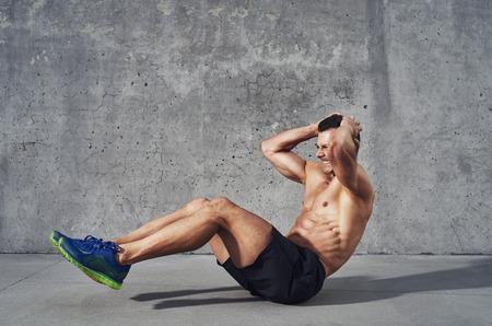 musculoso: Modelo de la aptitud ejercicio de sentadillas y abdominales. Construcción así muscular, cuerpo tonificado con seis paquetes sudoración. Copia espacio Foto de archivo