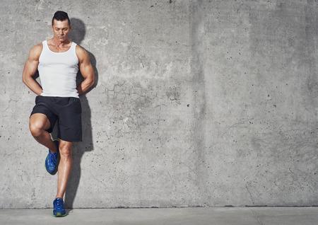 健身: 身體健康的人,肌肉的構建肖像,與灰色背景副本空間健身理念