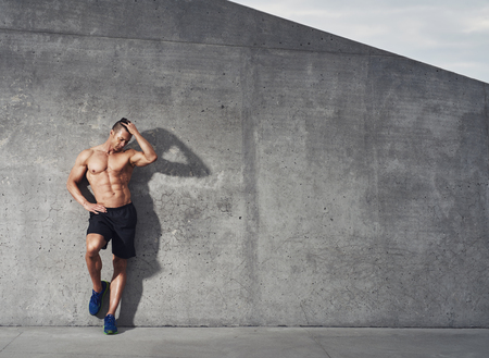 room for copy: Fit and healthy male fitness model portrait, standing against wall looking down, room for copy space.