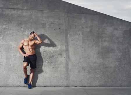 Geschikt en gezond mannelijk geschiktheids modelportret, dat zich tegen muur bevindt die neer, ruimte voor exemplaarruimte kijkt. Stockfoto
