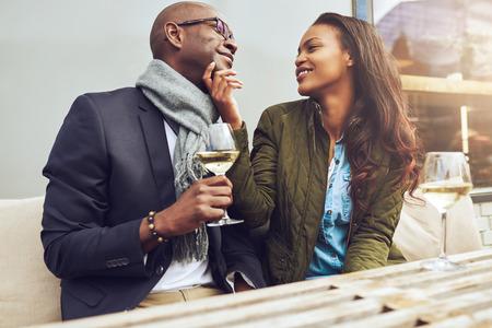 casados: Romántica pareja estadounidense en una fecha que liga juntos en una mesa de restaurante, ya que disfrutar de una copa de vino blanco