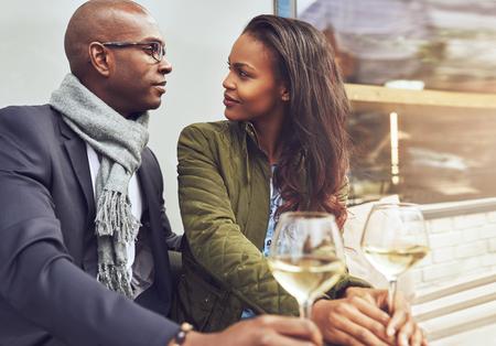Zwart paar met een gesprek in een cafe buitenshuis in het voorjaar