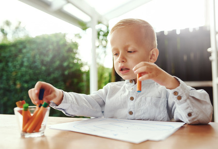 commence: Cute little blond boy selecting a colored wax crayon from a collection in a glass container as he prepares to commence drawing on sheets of white paper in front of him