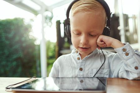 equipo de sonido: Adorable joven sentado con una computadora tablet escucha a su biblioteca de música con una feliz sonrisa de satisfacción en un conjunto de auriculares estéreo