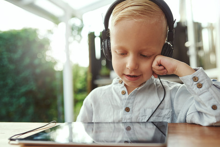 contentment: Adorable young boy sitting with a tablet computer listening to his music library with a happy smile of contentment on a set of stereo headphones
