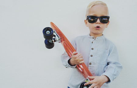 jaunty: Adorable hipster little boy with a skateboard wearing borrowed sunglasses from his Mum or Dad standing against a wooden wall giving the camera a funny cute expression