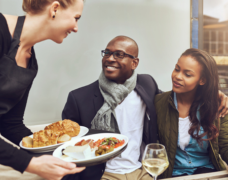 restaurant people: Romantic young African American couple sitting arm in arm being served dinner by a waitress as they sit at a restaurant table Stock Photo