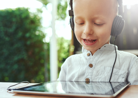 recorded: Adorable little boy listening to recorded music on his tablet computer using headphones with a delightful smile of contentment and pleasure, close up of his face