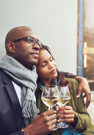 parejas de amor: Pareja africana Loving disfrutar de un momento de relax en un tierno abrazo en los brazos del otro sobre vasos de vino blanco