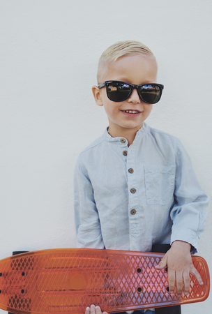 borrowed: Little boy in trendy over sized sunglasses borrowed from a parent standing clutching a skateboard looking at the camera with a cute charismatic smile