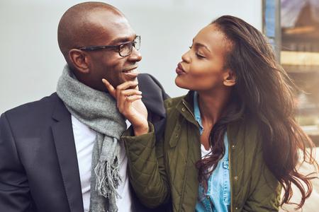 Flirtende jonge Afro-Amerikaanse vrouw tuitte haar lippen voor een kus en strelen het gezicht van een knappe man in glazen als ze samen genieten van een datum Stockfoto