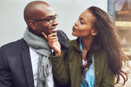 romantic: Flirting young African American woman pursing her lips for a kiss and caressing the face of a handsome man in glasses as they enjoy a date together Stock Photo