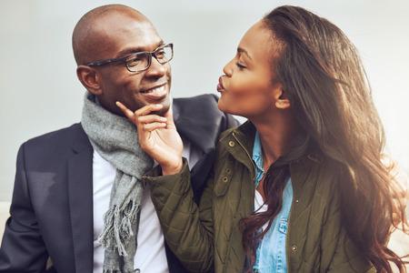mujeres sentadas: Coqueta joven mujer afroamericana en una cita con un hombre guapo en broma arrugando los labios para un beso Foto de archivo
