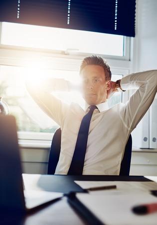 clave sol: Hombre de negocios joven empresario de horas extraordinarias de trabajo en su oficina mirando a su equipo con los brazos detrás de su cuello