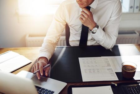 contabilidad: Hombre de negocios que trabaja en la oficina con ordenador portátil y documentos sobre su escritorio, el concepto de abogado consultor