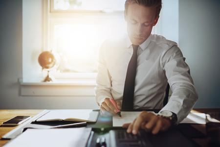 ejecutiva en oficina: Hombre de negocios ejecutivo que trabaja en las cuentas mientras se concentra y serio, vestido con camisa blanca y corbata Foto de archivo