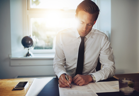 paralegal: White business man signing a contract and looking at documents at his office while looking serious