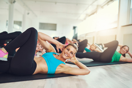 Smiling attractive young woman doing aerobics in the gym with a group of young women in a health and fitness concept Stock Photo - 47836176