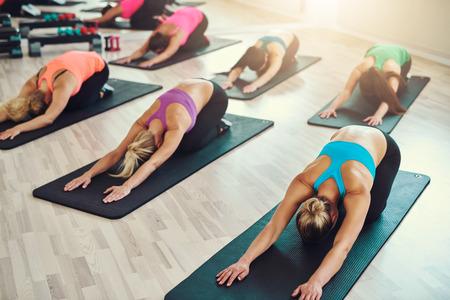 gimnasia aerobica: fitness, deporte, entrenamiento, yoga y concepto de la gente - sonriente mujer haciendo ejercicio en el gimnasio