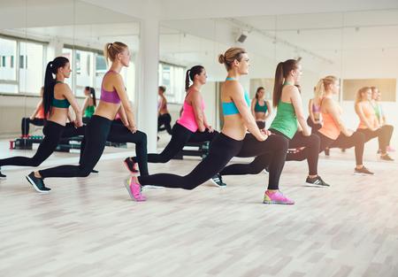 фитнес: фитнес, спорт, обучение, тренажерный зал и образ жизни концепция - группа людей, улыбаясь, осуществляющих в тренажерном зале