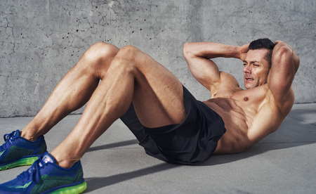 bodybuilder: Muscular man exercising doing sit up exercise. Athlete with six pack, white male, no shirt