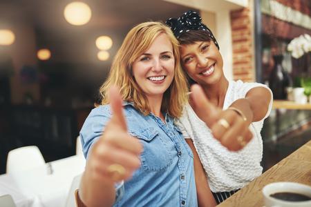 Zwei glückliche junge Freundinnen geben ein Daumen hoch Geste der Zustimmung und der Erfolg, wie sie sitzen Arm in Arm in einer Cafeteria genießen Kaffee zusammen