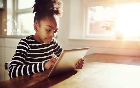 bambini: Ragazza nera con un divertente acconciatura afro seduto a un tavolo a casa la navigazione in Internet su un computer tablet con il chiarore del sole attraverso la finestra al suo fianco