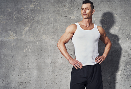 restitution: Fit and healthy man looking satisfied after workout, standing on grey background with room for text, copy space Stock Photo