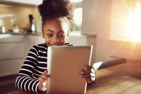 Happy little ethnic black girl sitting at home in the kitchen reading on a tablet computer grinning with pleasure, bright sun glow behind