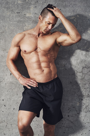 restitution: Fitness model portrait, muscular build fit and toned build. Relaxing after workout. no shirt Stock Photo