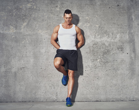 Muscular and fit man relaxing after workout, leaning against grey background, wearing white tank top and black shorts
