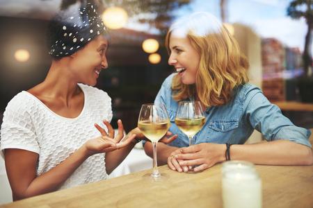 mujeres felices: Dos mujeres atractivas que disfrutan de una copa de vino blanco juntos en un bar sentado en una mesa riéndose y charlando con reflexiones sobre el cristal de la ventana, pareja multirracial joven